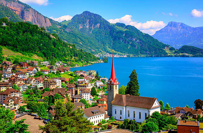 Little swiss town with gothic church on Lake Lucerne and Alps mountain, Switzerland.